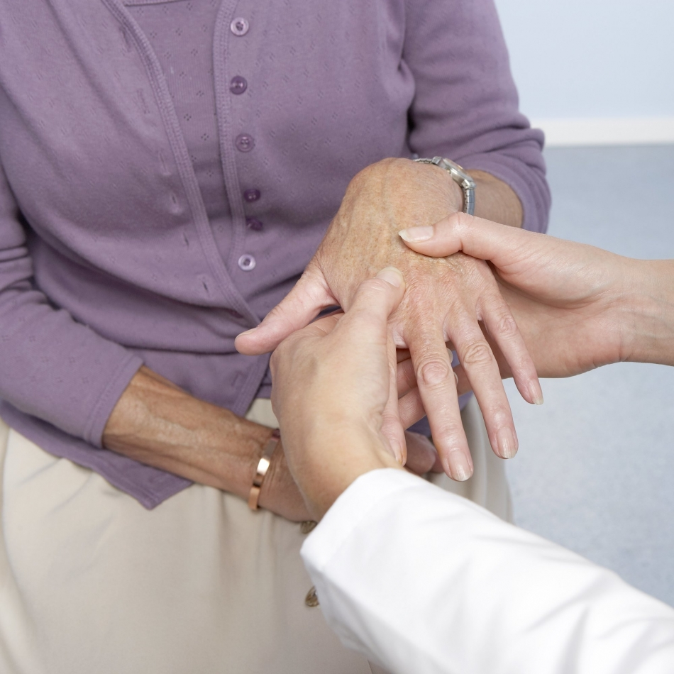 Rheumatoid arthritis. General practitioner examining a patient's hand for signs of rheumatoid arthritis. This condition is caused by the immune system attacking the body's own tissues, causing progressive joint and cartilage destruction. As the cartilage is worn away, new bone grows as part of the repair process. This causes stiffness and deformity of the fingers. Treatment is with anti-inflammatory drugs and physiotherapy.