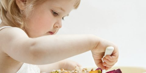 Adorable baby girl eating fresh vegetables; healthy eating for a baby