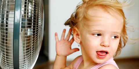 A little girl standing in front of fan