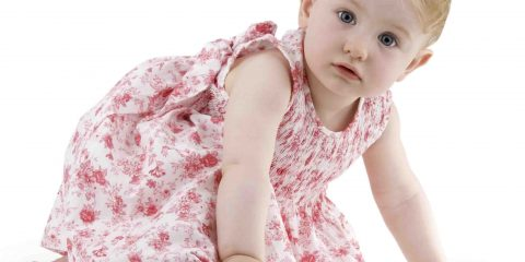 Infant in flowered dress on white background.