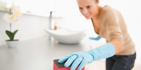 Closeup on young woman cleaning desk in bathroom
