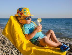 Boy kid in armchair with juice glass on beach against sea